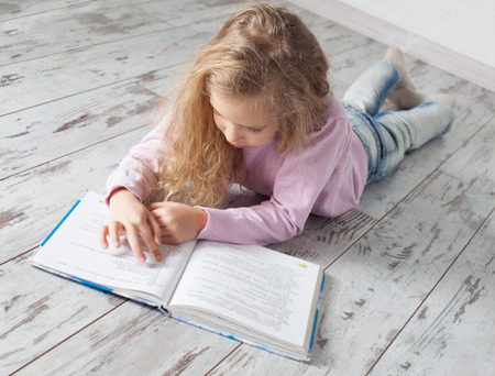 heated: Child reading book at home. Girl doing homework
