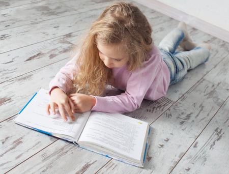 personas leyendo: Niño que lee el libro en casa. Chica haciendo la tarea