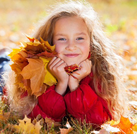 fall leaf: Girl at autumn. Child with leaf at park Stock Photo