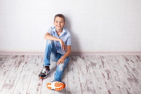 niños sentados: Chico feliz. Adolescente sonriente en la escuela