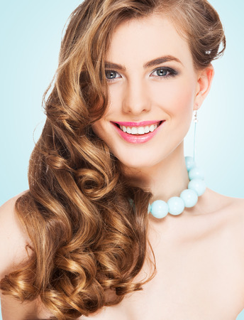 glamour nude: Beautiful woman with long curly brown hair. Glamour smiling female. Studio shot