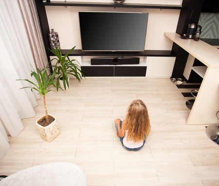 tv home: Child watching TV at home. Girl looking at television Stock Photo
