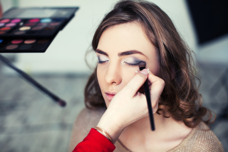 Woman applying makeup with brush Banque d'images