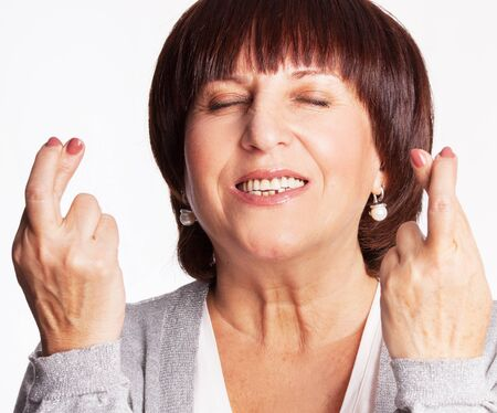 crossing fingers: Mature woman with crossed fingers. Female showing a gesture with hands. Luck, wish