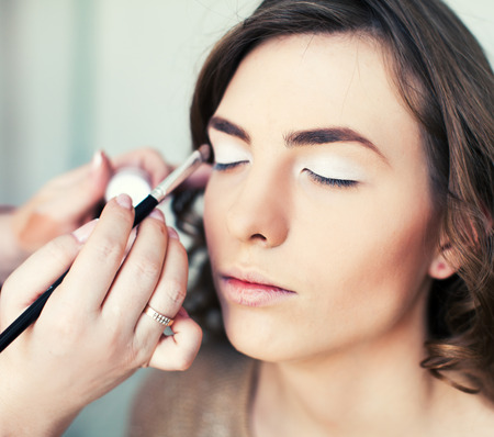 mujer maquillandose: Mujer que aplica maquillaje con el cepillo Foto de archivo
