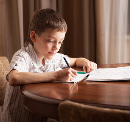 writing paper: Boy doing homework. Child education Stock Photo