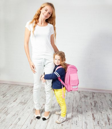 Mother helps her daughter get ready for school. Mom with child Stock Photo