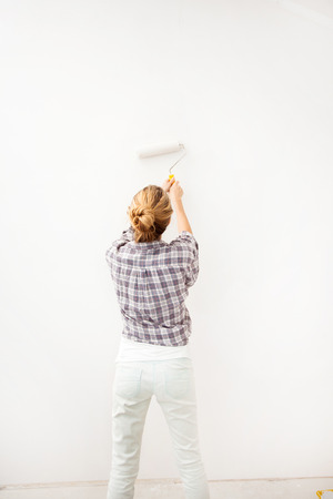 priming paint: Woman doing repairs. Female paints the wallpaper roll Stock Photo