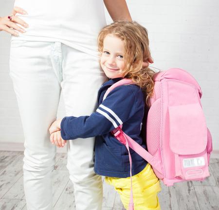 colegiala: Madre ayuda a su hija a prepararse para la escuela. Colegiala miedo de ir a la escuela Foto de archivo