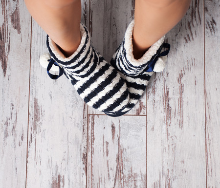 relaxing at home: Warm slippers on the background old white floor. Homeliness. Stock Photo