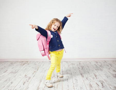 schoolbag: Little girl with schoolbag. Happy child on white Stock Photo