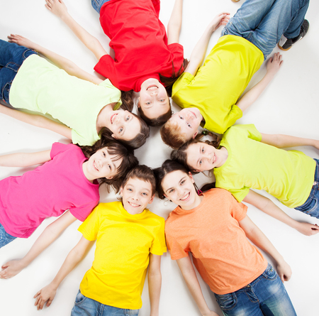 frendship: Happy group children isolated at white background. Smiling teen lying in a circle. Frendship boys and girls