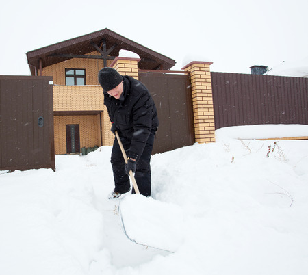 Man cleans snow shoveling around the house. Stock Photo