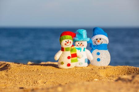 tropical christmas: Snowmans on sand near sea. Christmas decoration. Vacations