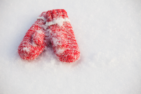 red gloves: Mittens in snow. Red knitted gloves in winter