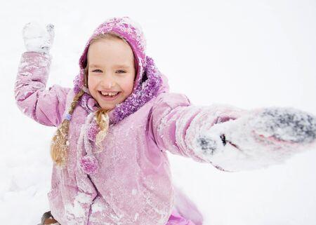 palle di neve: Bambino in inverno. Ragazza felice sulla neve. Giocare palle di neve