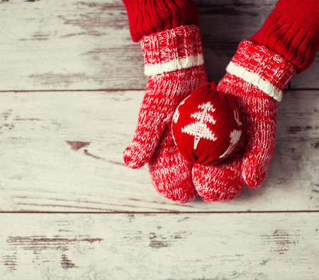 holding hand: Mitten with christmas ball on wood floor. Winter decoration Stock Photo