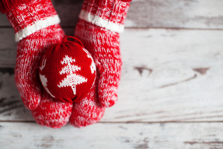 single object: Mitten with christmas ball on wood floor. Winter decoration Stock Photo