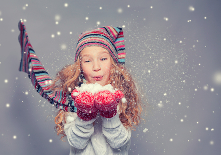 snows: Girl blowing on the snows. Happy child in winter clothes. Studio shot
