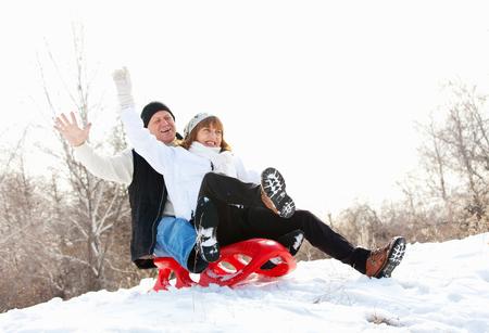 Mature couple sledding. Seniors couple on sled in winter park Stock Photo