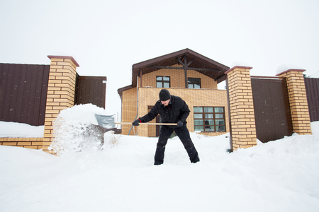 shoveling: Man cleans snow shoveling around the house. Stock Photo