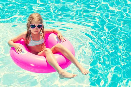 Mädchen auf aufblasbaren Ring im Schwimmbad. Urlaub Standard-Bild
