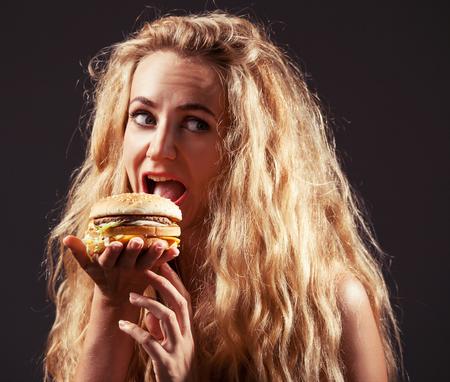 huge: Female with hamburger. Woman eating unhealthy food