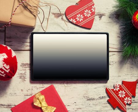 green background: Tablet on Christmas background. New Year holiday