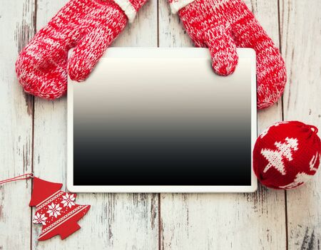 holding a christmas ornament: Tablet on Christmas background. New Year holiday