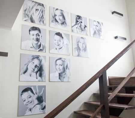 Family photos on the wall. Portraits of family stairwell Standard-Bild