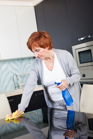 charwoman: Woman cleaning the kitchen. Adult woman washing house