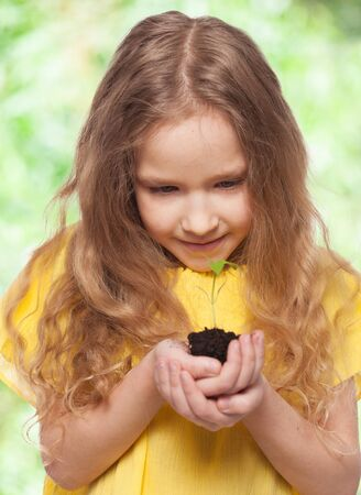 children eating: Child holding a sleedling. Girl with sprout
