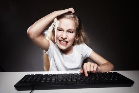decepci�n: El ni�o mira con decepci�n para ordenador. Adicci�n a la computadora Foto de archivo