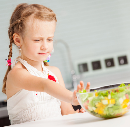 Little girl refuses to eat salad. Child looks with disgust for food Stock Photo