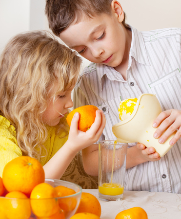 2 persons only: Children with oranges. Kids squeezed orange juice. Stock Photo