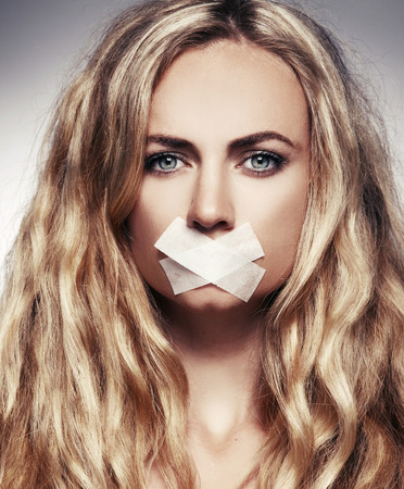 fear woman: Woman with mouth sealed plaster. Fear, silence, violence