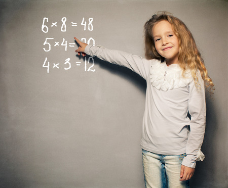 8 years: Child about school board. Girl showing blackboard Stock Photo