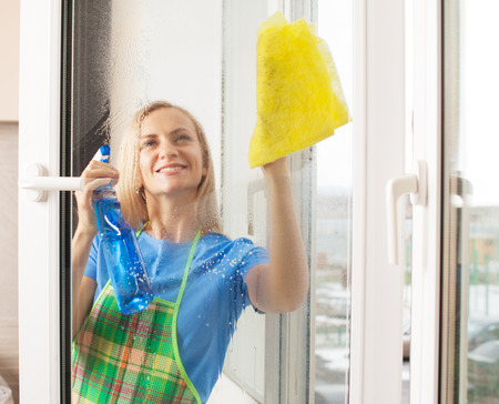 25 30 years: Woman washing window. Housewife cleaning window at home. Housework