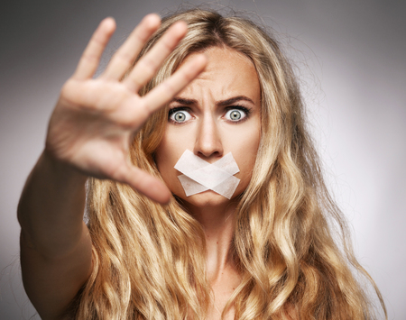 oppress: Woman with mouth sealed plaster. Fear, silence, violence