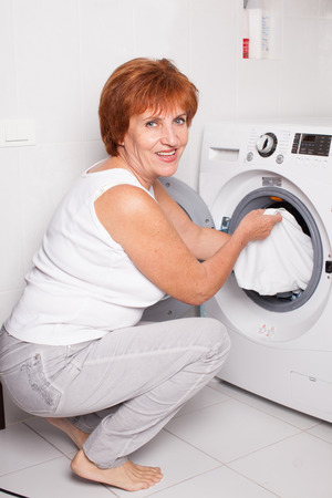 puts: Woman puts clothes in the washing machine at home