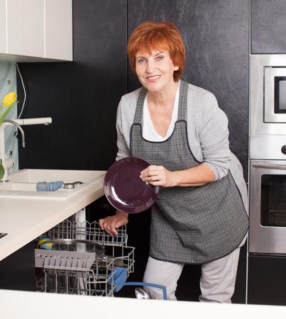 lavar trastes: Mujer doblando los platos en el lavavajillas. Mujer en la cocina. Tareas de la casa