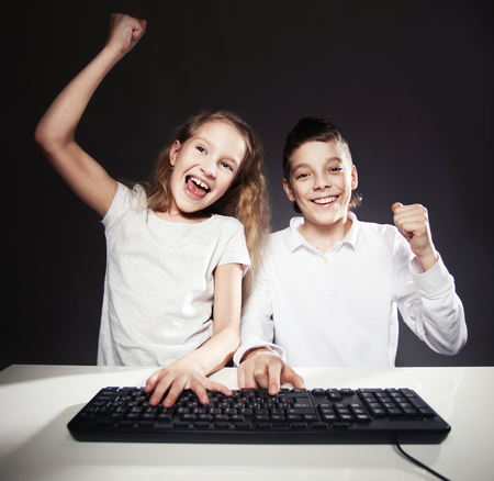 10 11 years: Children looking at a computer. fortune, win Stock Photo