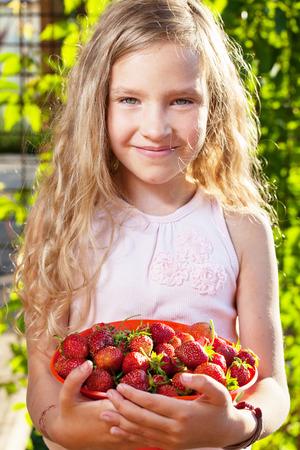 niña comiendo: Niño con la fresa. Muchacha con la fruta, bayas en el jardín
