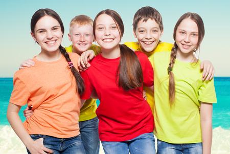amistad: Grupo feliz de los niños en el mar. Sonrisa adolescente. Niños y niñas Frendship Foto de archivo