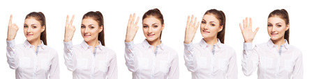 3 persons only: Woman at white background. Young female shows gesture. One, two, three, four, five Stock Photo
