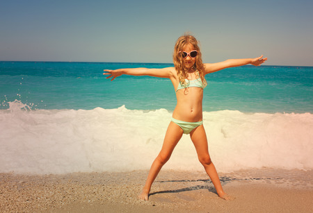 child laughing: Child on the beach. Girl at vacations on sea