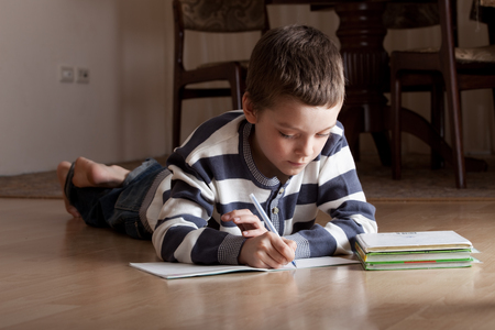 deberes: El niño hace las lecciones que mienten en el suelo