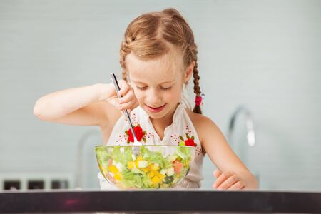 good food: Little girl eating vegetable salad in the kitchen. Child at home