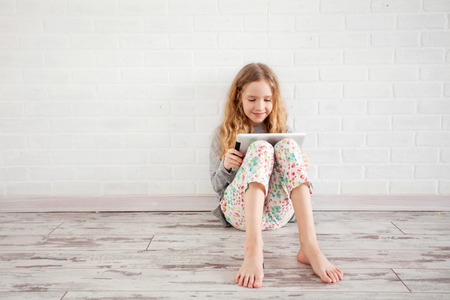 only: Child with tablet. Girl playing tablet at home Stock Photo