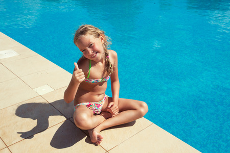Happy child at pool outdoors. Girl playing at summer. Tourist Stock Photo